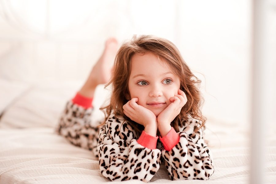 Smiling kid girl 5-6 year old lying in bed wearing leopard print pajamas in room. Looking away. Childhood. Resting in bed. Bed time.