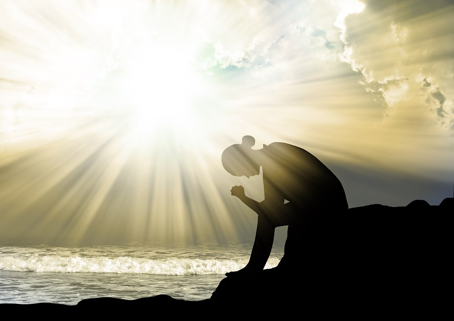 Silhouette of young girl praying to god