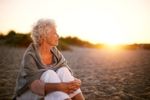 Old-Woman-Sitting-On-The-Beach-300x200