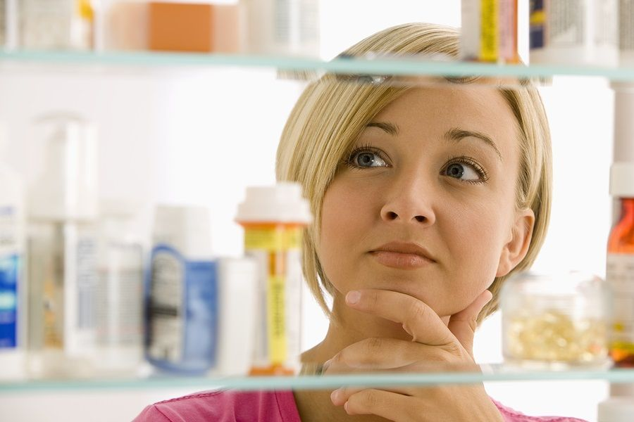 A young woman is looking through her medicine cabinet. Horizontal shot.