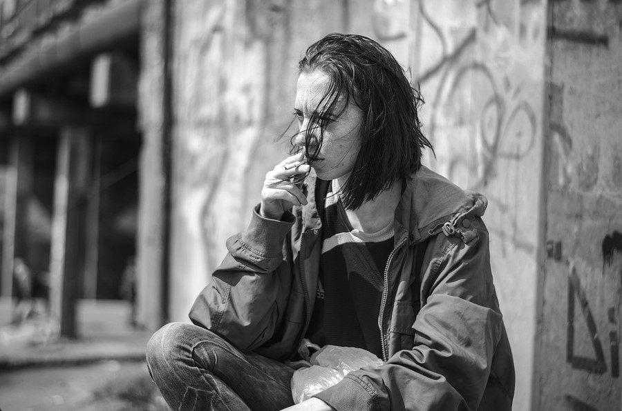 homeless beggar stilzhizni health social kontsept- Portrait of tired unhappy homeless hungry woman smokes a cigarette.